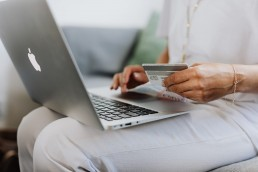 Woman paying with card on laptop